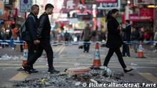 09.02.2016 *****epa05150596 Pedestrians walk past debris from a night of clashes between police and protesters in Mongkok district in Hong Kong, China, 09 February 2016. A crackdown on illegal street food hawkers during Chinese Lunar New Year escalated into what some witnesses described as a 'riot' in the district of Mongkok. Protesters, so-called localists' who campaign for varying degrees of independence for Hong Kong, launched sporadic brick and bottle attacks on police, who retaliated with pepper spray. Police fired 2 warning shots. EPA/JEROME FAVRE +++(c) dpa - Bildfunk+++ © picture-alliance/epa/J. Favre