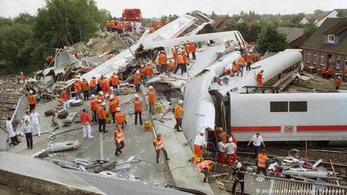 Archivaufnahme: An einer durch einen Intercity-Zug total zerstörten Straßenbrücke in Eschede liegen am 3.6.1998 die verunglückten Waggons kreuz und quer. Bisher wurden 90 Tote geborgen, zwei Menschen erlagen in der Nacht ihren Verletzungen. Mit einer verzweifelten Bergungsaktion unter schwierigsten Bedingungen versuchen Helfer, noch Überlebende der Zugkatastrophe zu retten, bislang erfüllten sich ihre Hoffnungen aber nicht. Mehrere Waggons des ICE 884 Wilhelm Conrad Röntgen auf der Strecke München-Hamburg waren am 3. Juni aus bislang immer noch ungeklärter Ursache am Escheder Bahnhof bei Tempo 200 aus den Schienen gesprungen. Vier Wagen prallten mit enormer Wucht gegen das Brückenfundament. Die Straßenbrücke stürzte ein und begrub Teile des Zuges unter sich. (Foto: picture alliance/Holger Hollemann)