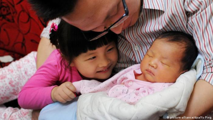 Chinese father holding his newborn son and daughter