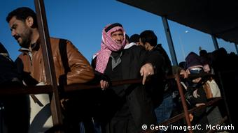 Men wishing to return to Syria, from Turkey, wait in line to pass through a border gate.