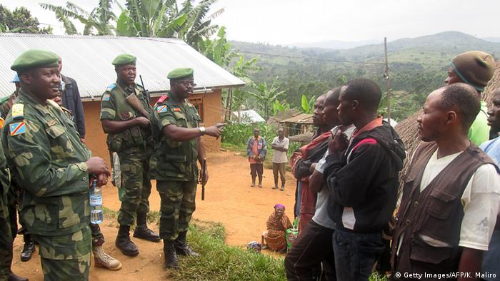 Members of DRC army in conversation with local residents after a rebel attack in Miriki, north of Goma