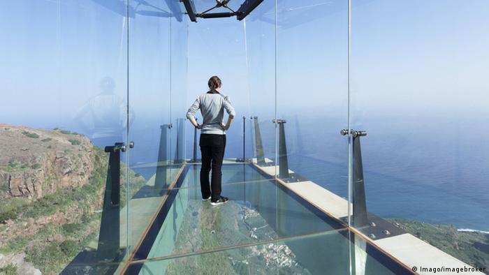 Frau steht in einem Glaskasten