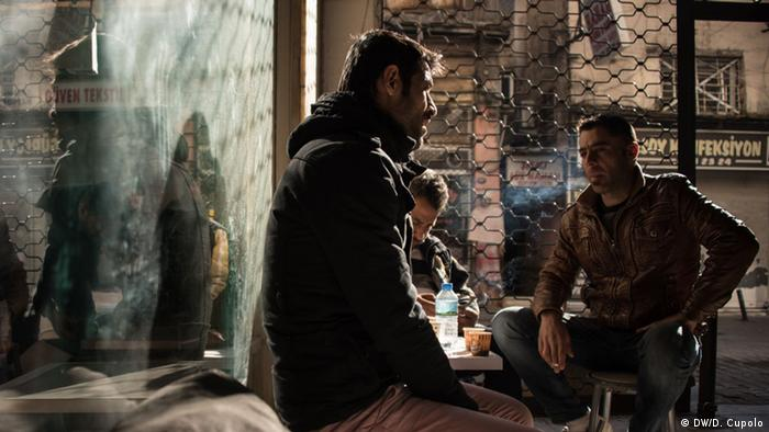 Syrian refugees Abdulrahman Ebrahim and Maher Mahmood sit with a friend at a café in Izmir's Basmane district