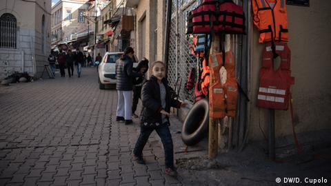 Children play near life jackets being sold on a street corner