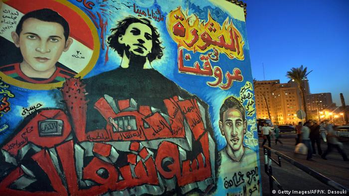 Sebuah mural yang menampilkan pemuda dan slogan dalam bahasa Arab