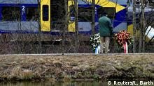 10.02.2016 *** A man stands in front of wreaths at the site of two crashed trains near Bad Aibling in southwestern Germany, February 10, 2016. Ten people were killed and at least 81 injured on Tuesday when two passenger trains collided head-on at high speed in remote countryside in southern Germany. One passenger was still missing, police said, and 18 of those injured were in a serious condition. REUTERS/Lukas Barth © Reuters/L. Barth