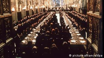 Students sitting at a table of a large hall in a film still from a Harry Potter movie.