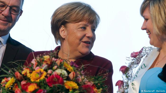 German Chancellor Angela Merkel stands with the Flower Fairy at a Valentine's Day celebration