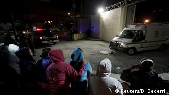 An ambulance leaves the prison compound in Monterey as prison relatives watch from behind barricades.