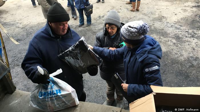 Сотрудники Управления ООН по делам беженцев раздают местному населению теплую одежду
