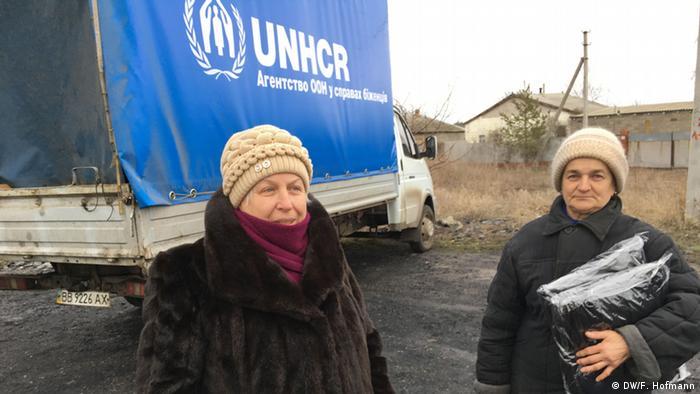 Сотрудники Управления ООН по делам беженцев раздают местному населению гуманитарную помощь