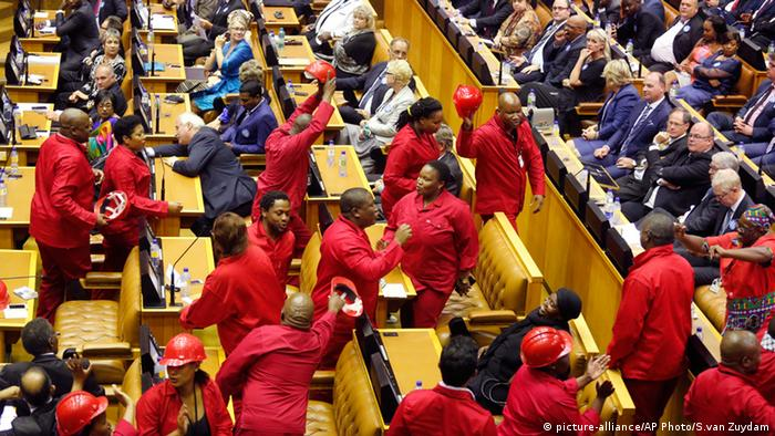 Julius Malema, center, leader of the Economic Freedom Fighters walks out of parliament during President Zuma's speech.