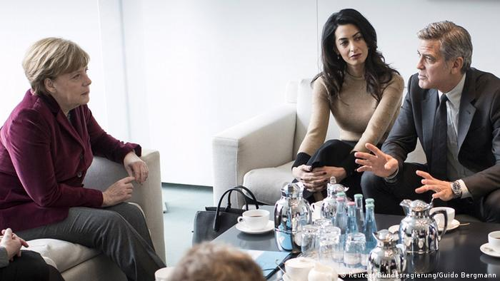 Chancellor Angela Merkel sits across from George Clooney and his wife Amal during a meeting in Berlin on February 12, 2016
