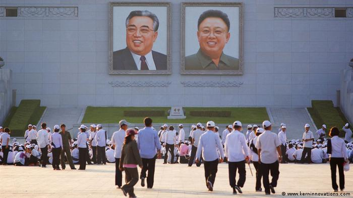 Tourists in front of a building with large pictures of Kim Il Sung and Kim Jong Il. (Photo: www.kerninnovations.com)