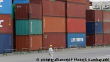 In this April 22, 2015 photo, a port worker walks by cargoes piled up at a container terminal in Tokyo. Japan's trade deficit narrowed in September to 114.5 billion yen ($955 million) but exports fell short of expectations as demand from China waned. The trade data released Wednesday, Oct. 21, 2015, showed exports rose only 0.6 percent from the year before to 6.42 trillion yen (53 billion) while imports fell 11 percent, to 6.53 trillion yen ($54 billion). (AP Photo/Shizuo Kambayashi)
