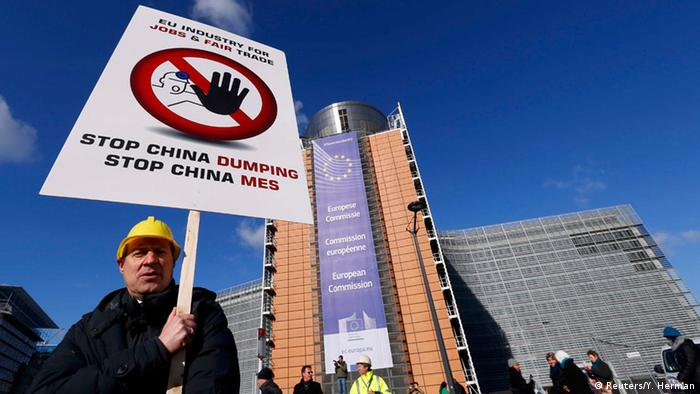 A steelworker pickets while the European Commission meets with industry leaders