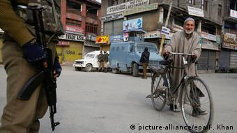 A Kashmiri Muslim walks along with his bicycle as an Indian soldier stands guard
