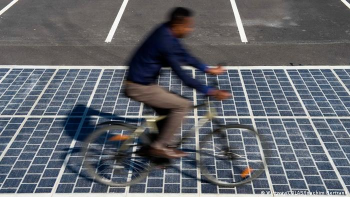 Wattway promotional photo showing man riding bicycle on solar roadway (Photo: COLAS - Joachim Bertrand)