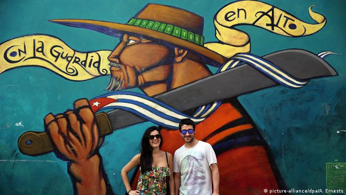 Tourist couple posing beside a graffiti, Havana, Cuba,