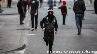 A pro-democracy protester, wearing a hat that covers all but his eyes runs down a street in Bahrain.