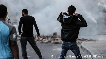 Three protesers, with their backs to the camera, watch as smoke fills the street.
