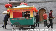 Two Chinese brothers, Wang Kai and Wang Rui, take their mother in a homemade carriage to Fuzhou on March 2, 2010. Their 81-year-old mother, Wang Yuxia, sticks her head out the window to see the views in the capital city of China's Fujian province. To go with story 'Fueled by filial piety' by Hu Meidong, Zhu Xingxin and Wang Qian; Copyright: picture alliance/ASIAN NEWS NETWO/Zhu Xingxi