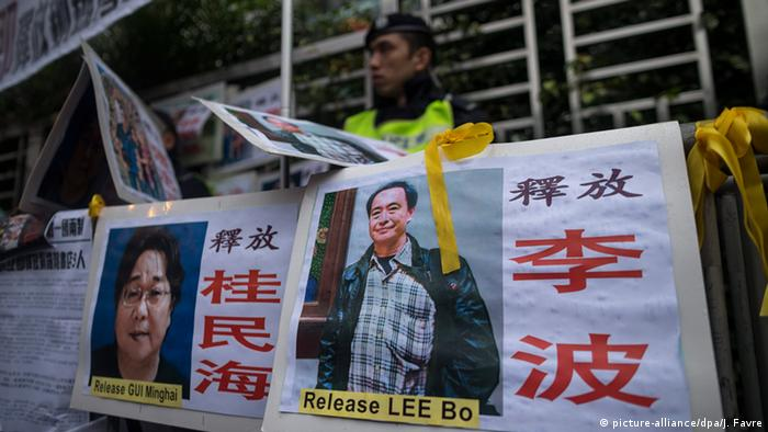 Photographs of the missing bookstore shareholders Gui Minhai, (L), and Lee Bo, are taped to barriers outside the China Liaison Office during a protest in Hong Kong, China