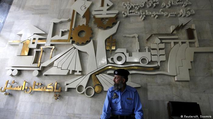 A security guard sits in front of a wall with signs and slogans at the operation building at the Pakistan Steel Mills (PSM) on the outskirts of Karachi, Pakistan, February 8, 2016