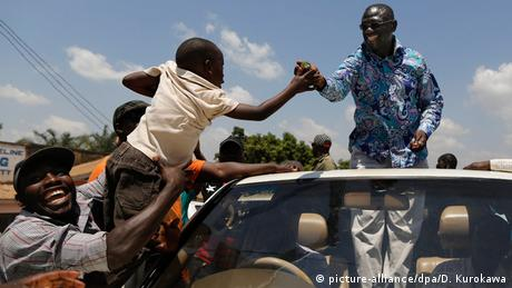 Uganda Kampala Oppositionsführer Kizza Besigye im offenen Wagen grüßt Kind