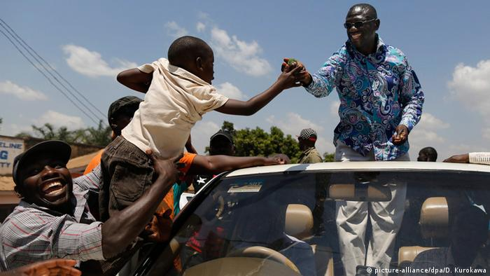 Kizza Besigye greeting a child (photo: picture alliance)