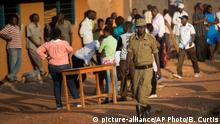 18.02.2016++++++++ A policeman patrols as voters wait patiently at a polling station where an hour and a half after voting was due to start, ballot boxes and papers had not yet arrived, in Kampala, Uganda Thursday, Feb. 18, 2016. Ugandans went to the polls Thursday as President Yoweri Museveni, in power for 30 years, is facing his tightest race ever with opposition leader Kizza Besigye his main challenger. (AP Photo/Ben Curtis) picture-alliance/AP Photo/B. Curtis