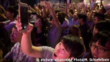 A fan takes a selfie of celebrities at a red carpet event for the premiere of the movie Tiny Times 4 in Beijing, Wednesday, July 8, 2015. Stars attended the premiere of the expected final installment of one of China's most successful movie franchises, whose depiction of the lives and loves of four young women has garnered many fans among the young cinema-going audience. (AP Photo/Mark Schiefelbein)