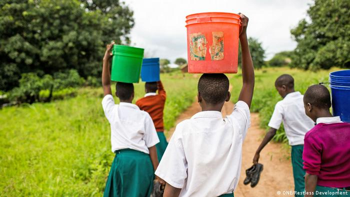 A group of young Tanzanian girls carrying water on their heads.