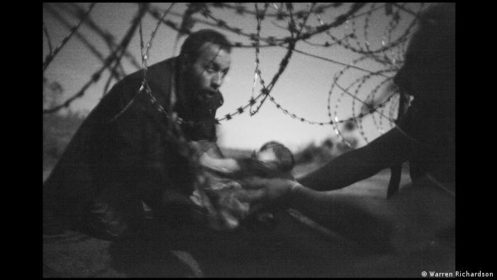 World Press Photo 2015: Flüchtlinge an den Stacheldraht Grenzzaun bei Röszke Ungarn (Foto: Warren Richardson)