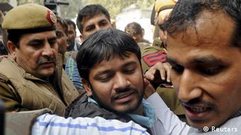 Jostled by media and protesters, Kanhaiya Kumar (C), head of the student union at Delhi's Jawaharlal Nehru University (JNU), is escorted by police outside the Patiala House court in New Delhi.