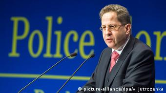 Hans-Georg Maaßen, head of the BfV, gives a lecture with a large 'Police' sign behind him.
