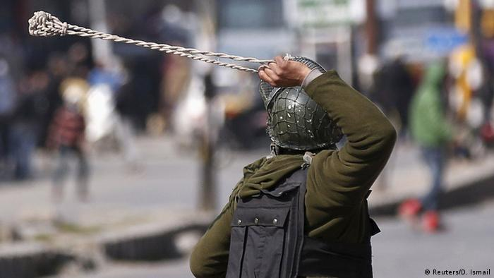 An Indian policeman uses a slingshot to hurl stones towards Kashmiri demonstrators.
