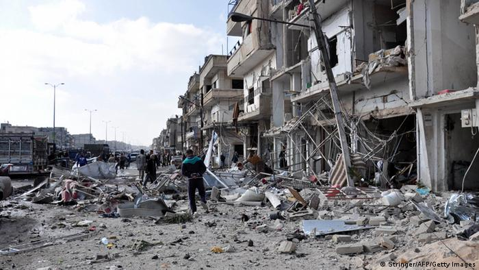 Syrians inspect the damage at the site of a double car bomb attack in the Al-Zahraa neighborhood of the central Syrian city of Homs in February