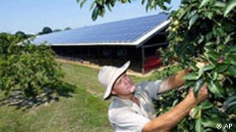 Farmer in New Jersey in front of barn with solar panels on roof