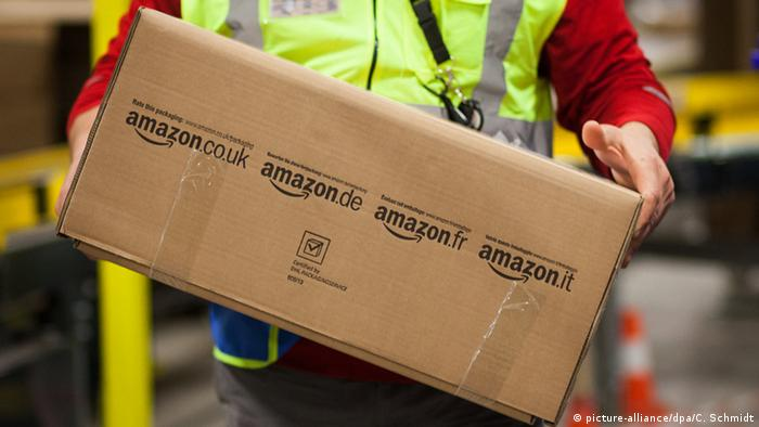 Worker holds Amazon package. Photo credit: picture-alliance/dpa/C. Schmidt