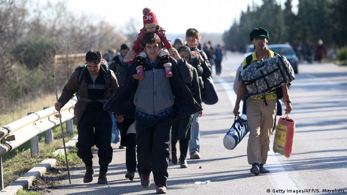 Migrants and refugees walk along a road to cross the Greek-Macedonian border near the village of Idomeni
