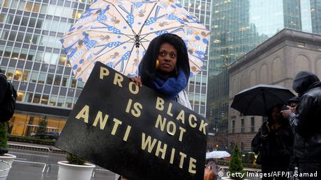 Woman holding a sign pro black is not anti white