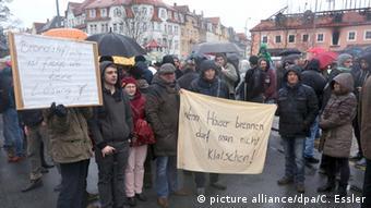 Активисты перед сгоревшим общежитием в Баутцене