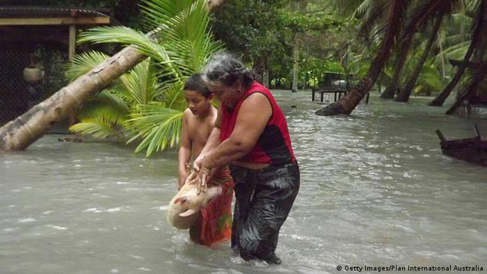 A woman and boy carry a pig through floodwaters on the island of Tuvalu during Cyclone Pam on March 13, 2015 (Getty Images/Plan International Australia)