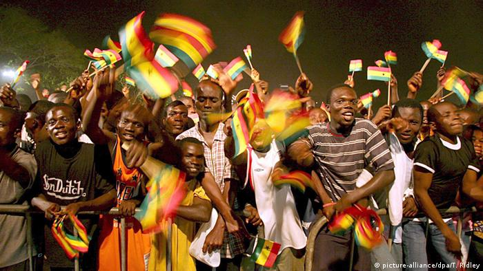 Young people waving Ghana's red, yellow and green flags at a concert in Accra
