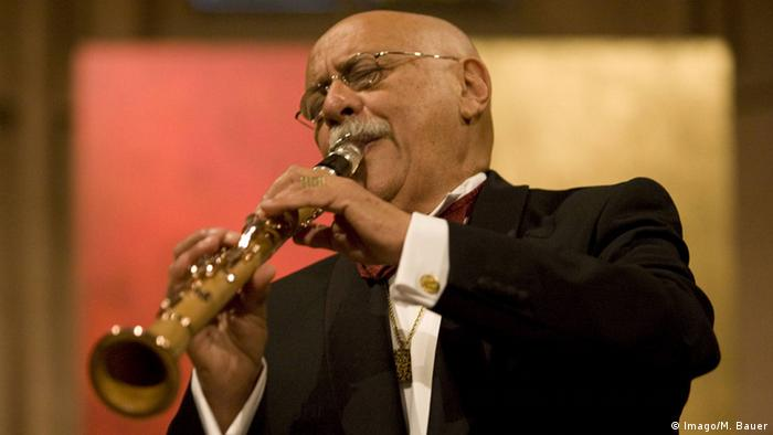 a man wearing glasses plays the clarinet