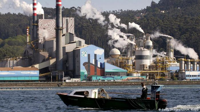 A fishing boat passes the Ence cellulose factory on the banks of the river Pontevedra in Pontevedra, 19 April 2006 (Photo: MIGUEL RIOPA/AFP/Getty Images)