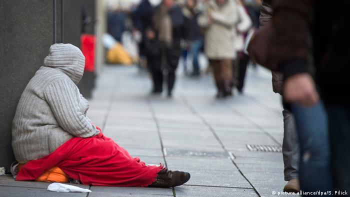 A homeless person sits on the street in Stuttgart, Germany