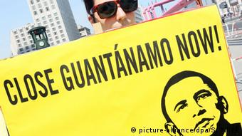 A demonstrator holds a sign reading 'Close Guantanamo now'