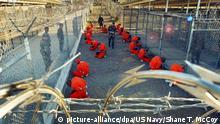 HANDOUT - ARCHIV - In orangefarbene Overalls gekleidete Häftlinge knien im Camp X-Ray auf dem US-Marinestützpunkt Guantanamo Bay auf Kuba am 18.01.2002 auf einem von der US-Armee herausgegebenen Archivfoto. Foto: Shane T. McCoy/US Navy/dpa (zu dpa Problem Guantánamo - Menschenrechtler beharren auf Schließung vom 10.11.2015 - ACHTUNG: Nur zur redaktionellen Verwendung bei Nennung der Quelle: Foto: Shane T. McCoy/US Navy/dpa) +++(c) dpa - Bildfunk+++ +++ (C) picture-alliance/dpa/US Navy/Shane T. McCoy
